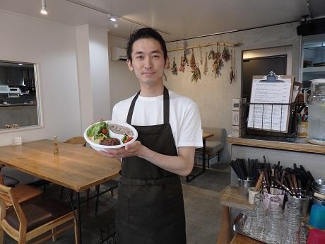 店長の生駒俊典さん。手にしているのは近日提供予定のテークアウト用プレート
