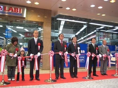 ヤマダ電機・一宮忠男代表取締役副社長兼COO(右から3番目)、品川区長・浜野健さん(左から3番目)らがテープカットを行った