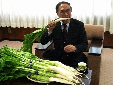 品川カブをかじる濱野健区長。15本の品川カブを目の前に「こんなにたくさん食べられないな」と笑う。