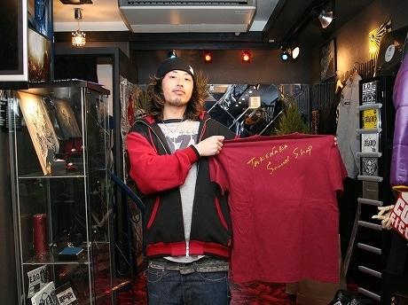 「TAKENAKA SOUNDSHOP」オリジナルTシャツを手にする店長の立川さん。黒で統一した店内は、スタッフ全員による手づくり。