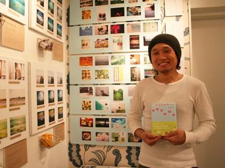 神戸在住の作家、季東将司さん。自身のデビュー作「かわいいカノン」を手に。