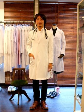 国内でもこの店舗でしか取り扱っていないというBEAMSの白衣「メンズドクターコート」(18,900円)を記者が試着。金子さんは「まだネット販売もされていない商品。個人で購入できるのは都内で当店だけ」と話す。