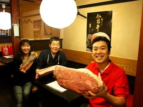 大きな牛肉の塊を手にする中村店長とスタッフ。