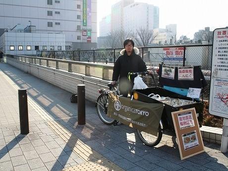 三輪自転車で産直野菜を販売する助田さん。「オーガニカ東京」のコンセプトは「安心・安全な全国のこだわり食材を直送販売!~Tokyoから発信する新しい産直のカタチ~」。
