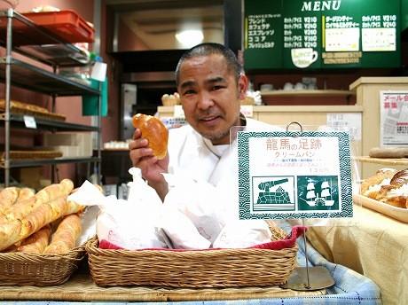 「カフェ・ロティー」の渡辺店長。「赤ちゃんの足みたい」と言われるという「龍馬の足あとパン」を手に。