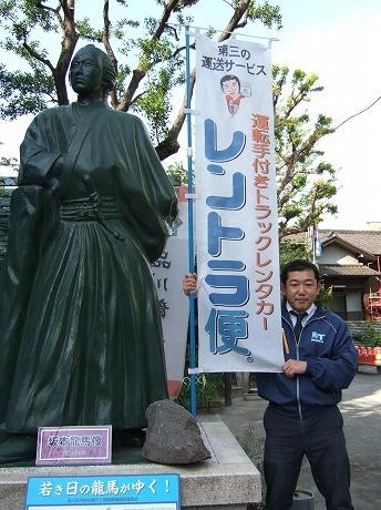 写真提供=ハーツ 京急立会川駅前の龍馬像の前でアピールする山口社長。