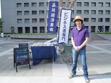 「リヤカーブックス」の木村店長。品川駅港南口近くの「NTT品川ツインズオフィス棟」前の広場で営業している。