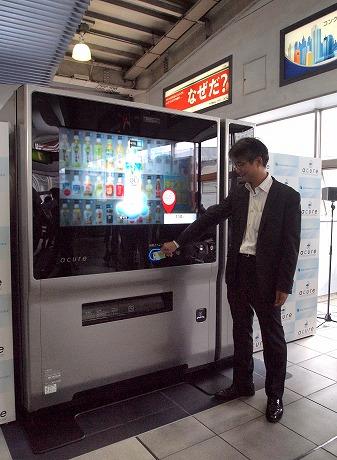 「次世代自販機」のデモンストレーションを行う田村修社長。場所は中央改札口近く、山手線ホーム乗り場の上あたり。もう1台は京浜東北線ホーム上に設置している。