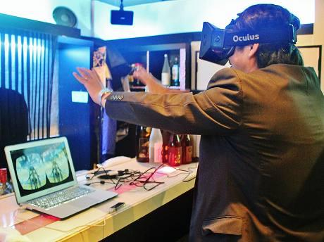 仮想3D空間の初音ミクに向かって手を動かす男性参加者