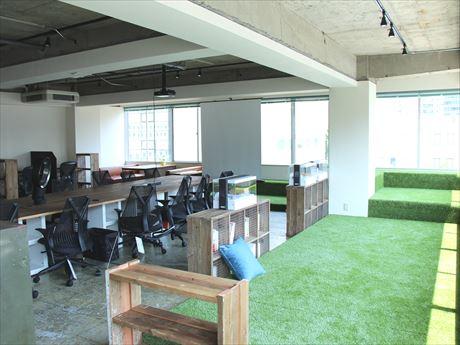 明るく開放的な人工芝スペース。中央のテーブルにはセイルチェアを配備