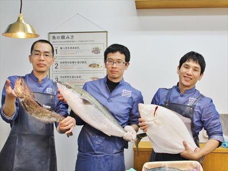 鮮魚を持つスタッフ