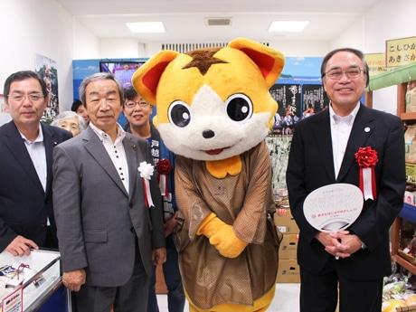 戸越銀座商店街のマスコット・戸越銀次郎を挟んで、濱野健品川区長(右)と坂本憲男坂井市長(左から2番目)