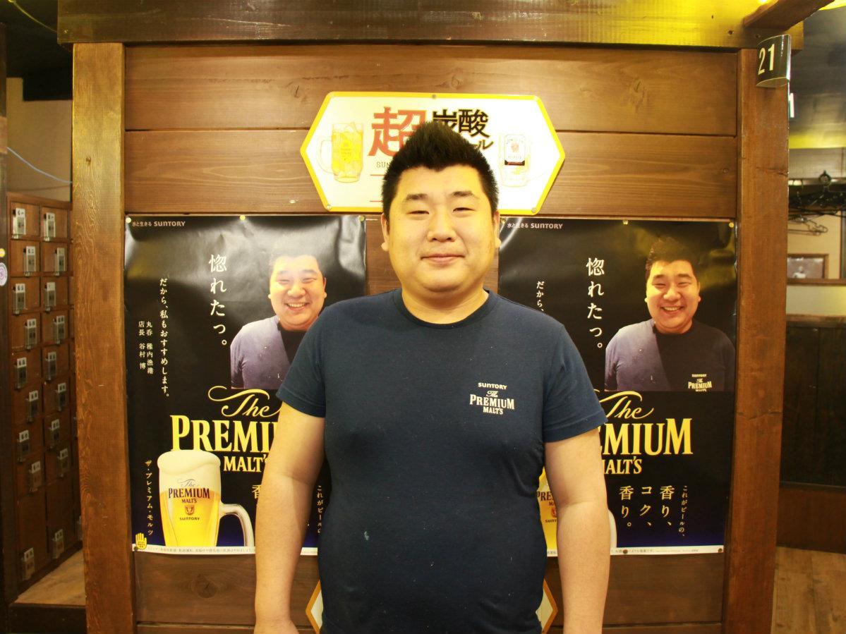 店長の谷村博さんとポスター