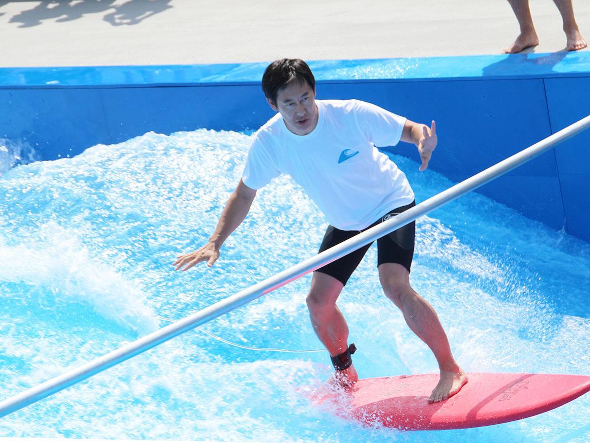屋外人工サーフィン施設でサーフィンに挑戦するスポーツ庁長官の鈴木大地さん