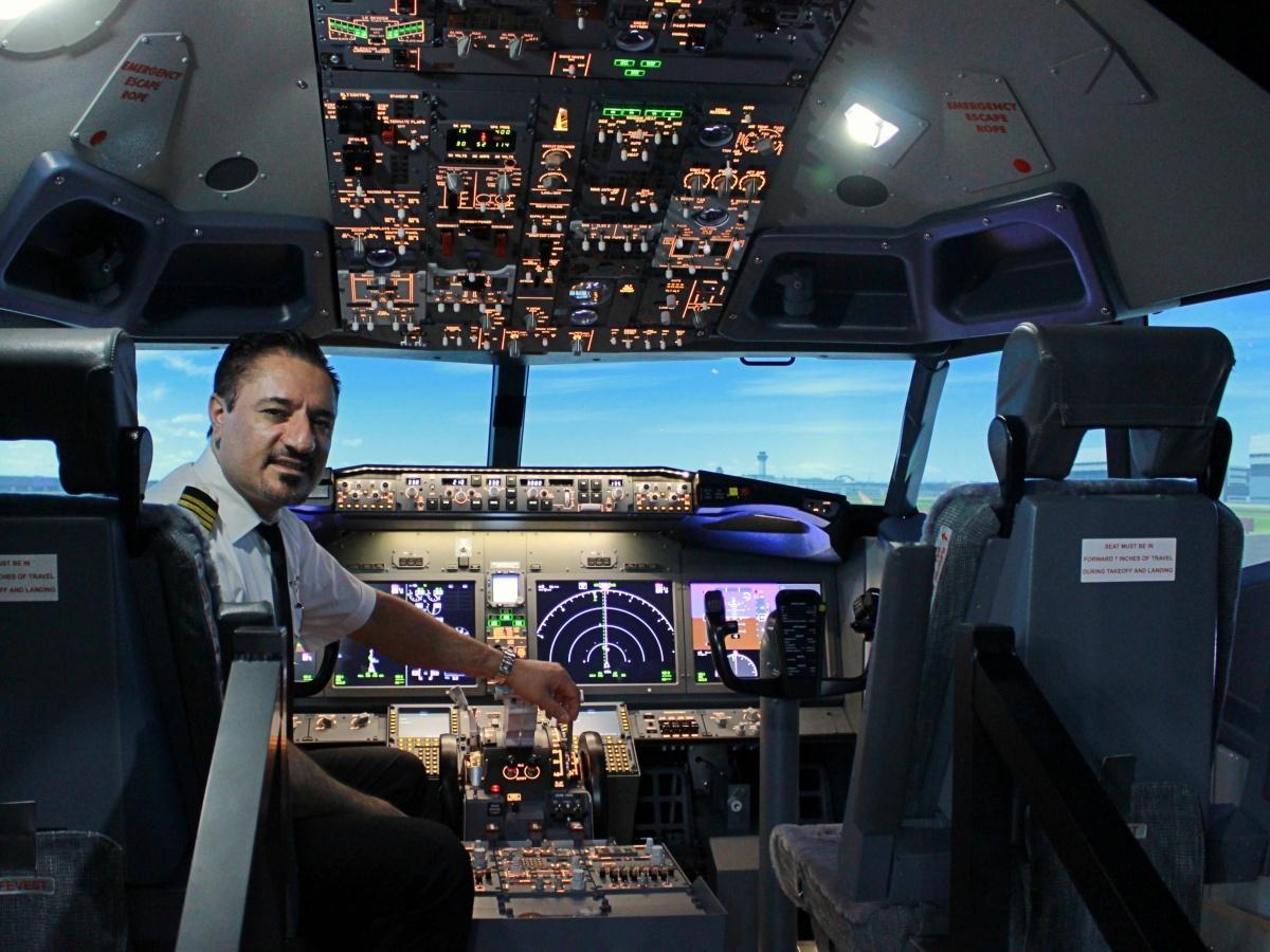 フライトシミュレーター「B737MAX」の操縦席に座る、代表のアルパ・アブドラさん
