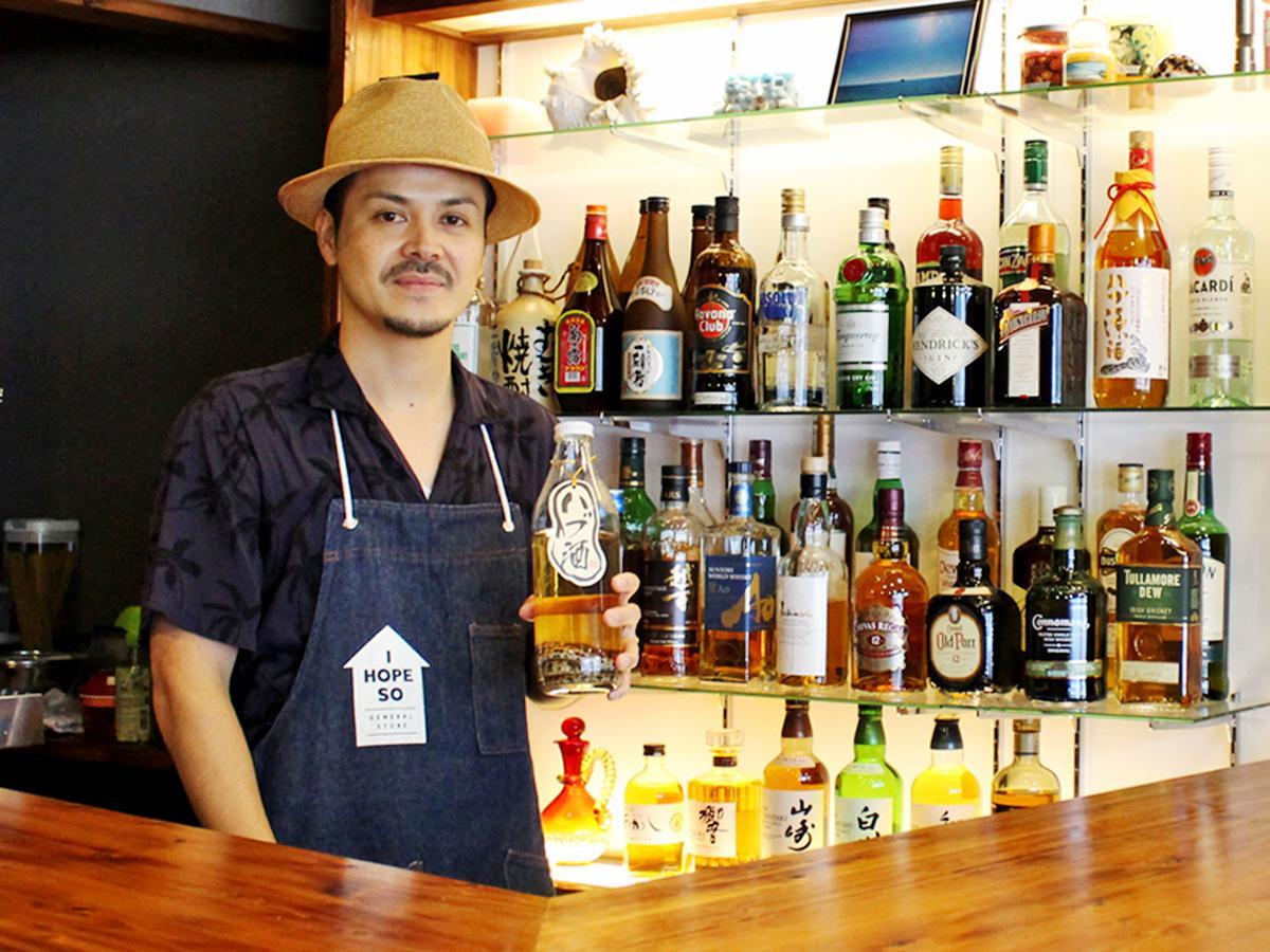 ハブ酒を持つ沖縄出身の店主・川上恵世さん