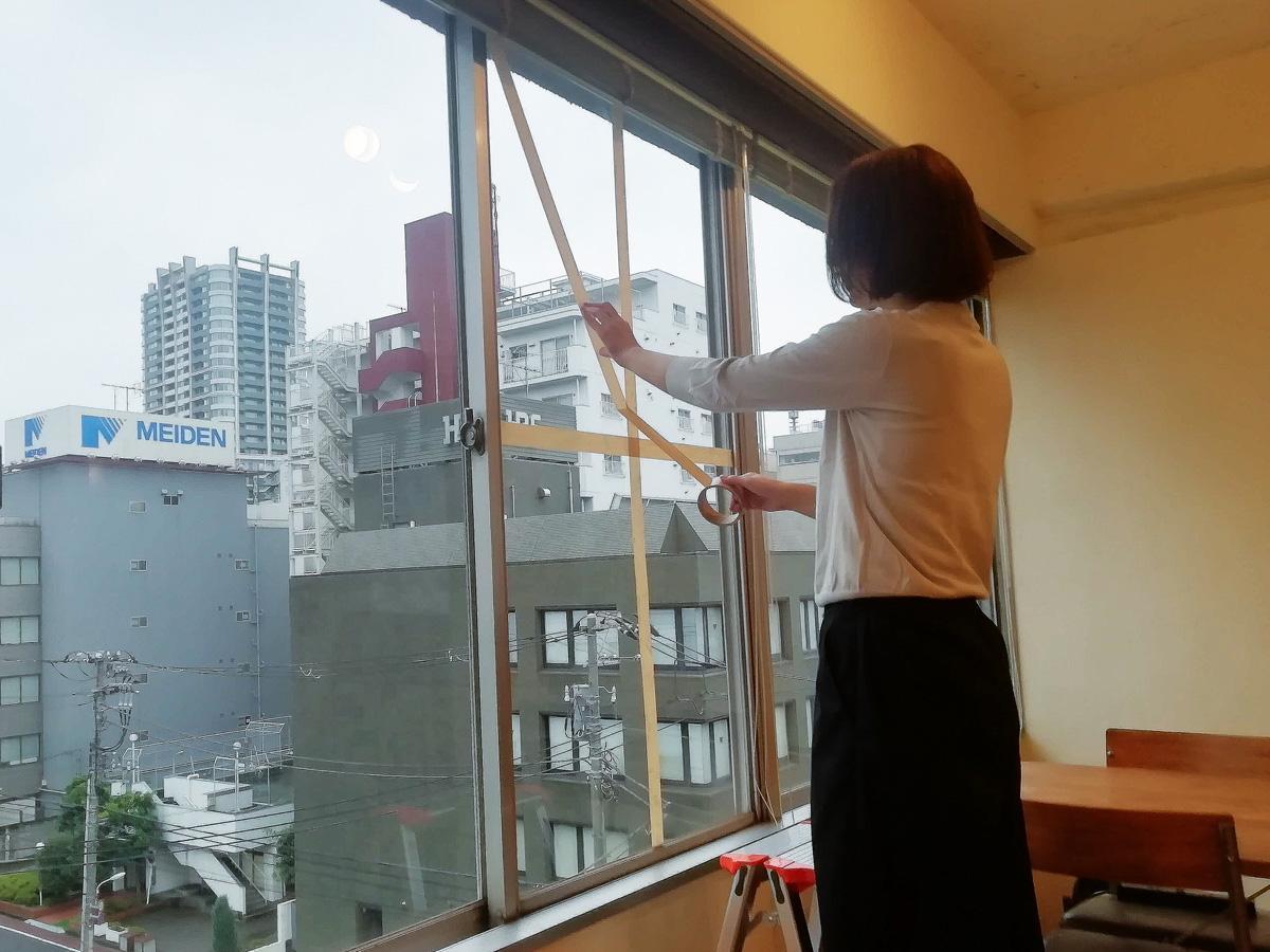 養生テープを窓に張り、台風に備える品川経済新聞編集部