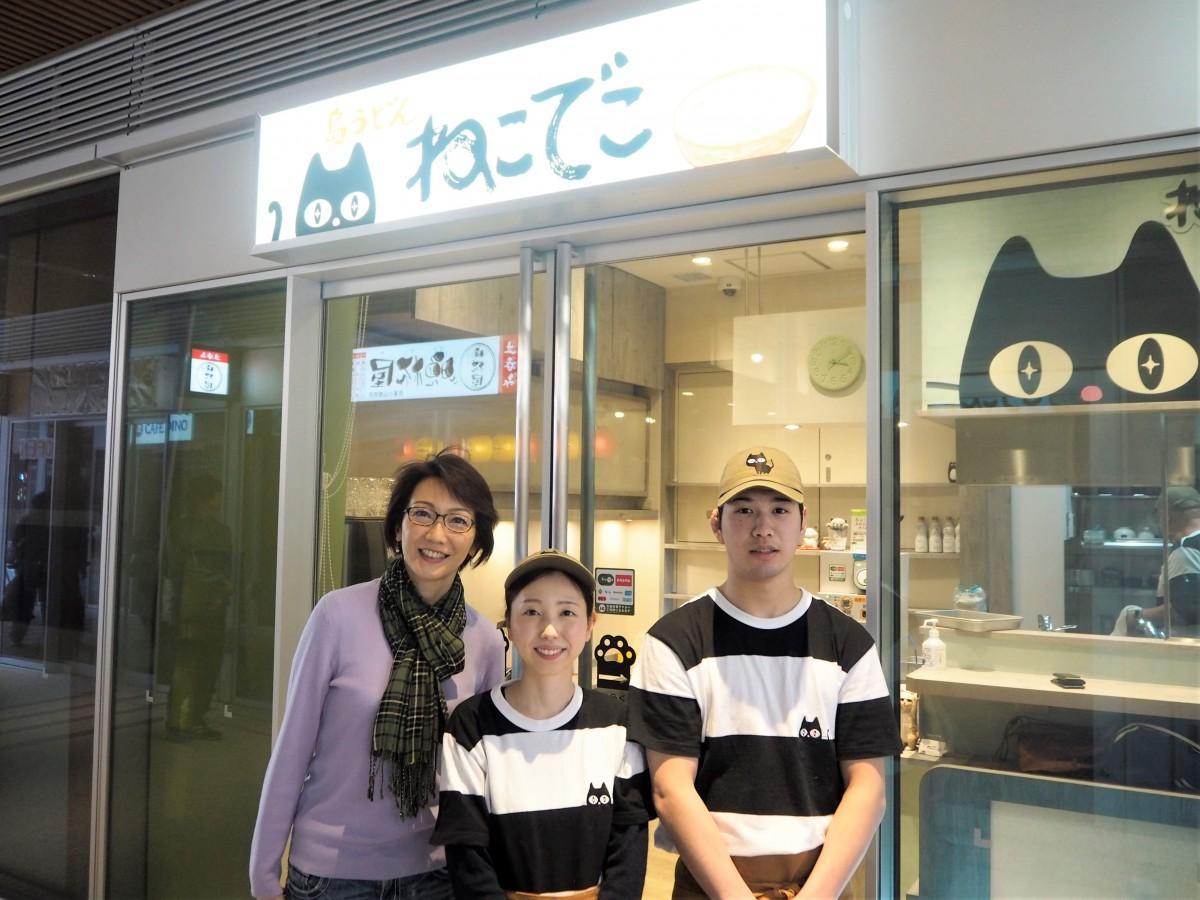 「島うどん ねこでこ」の外観。左からオーナーの向井亜紀さんと男女アルバイトスタッフ