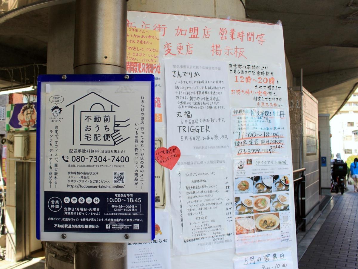 不動前駅前の高架下にある商店街加盟店の営業時間変更を知らせる掲示板