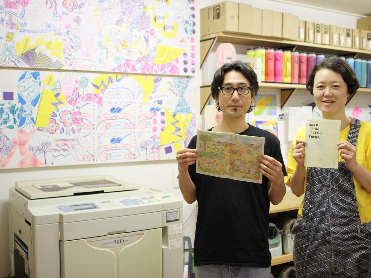 リソグラフ印刷機と菅野信介さん(左)、安藤僚子さん