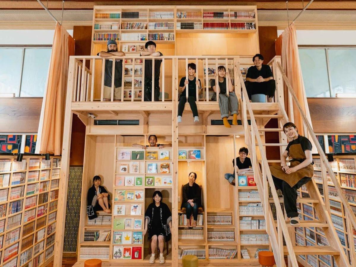 フリースペースに設置した巨大本棚と運営メンバー(提供:東京浴場)