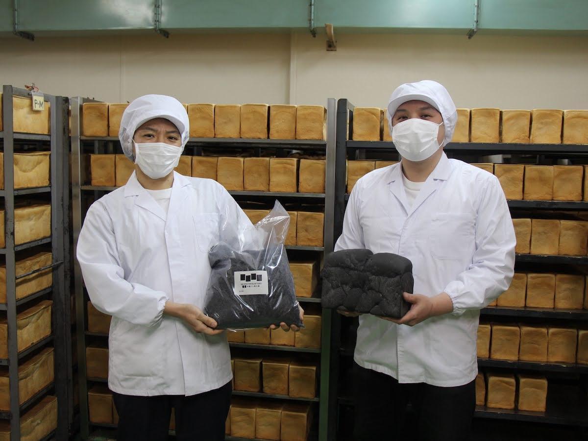 真っ黒なパン粉を手に持つ3代目社長の中林正一さん(左)と工場長の中林良太さん