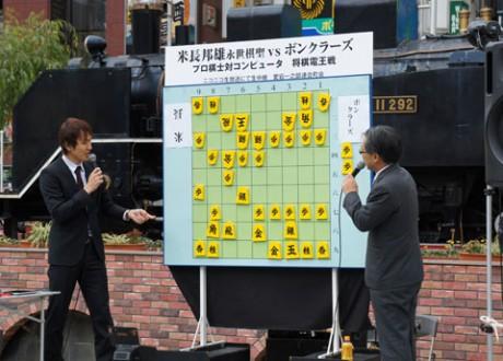 寒さに耐えながら解説を聞き入る将棋ファン。「最近はコンピューターが優秀で勝つことが難しくなっている」(西尾六段)という。