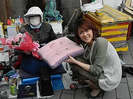 路上靴磨きの母・中村幸子さんに、ひと足早い母の日のプレゼントを手渡すあさみさん