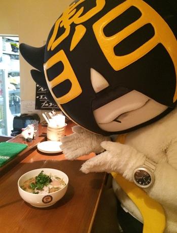 豚骨風パスタ麺を紹介する虎ノ門のご当地キャラ「カモ虎課長」