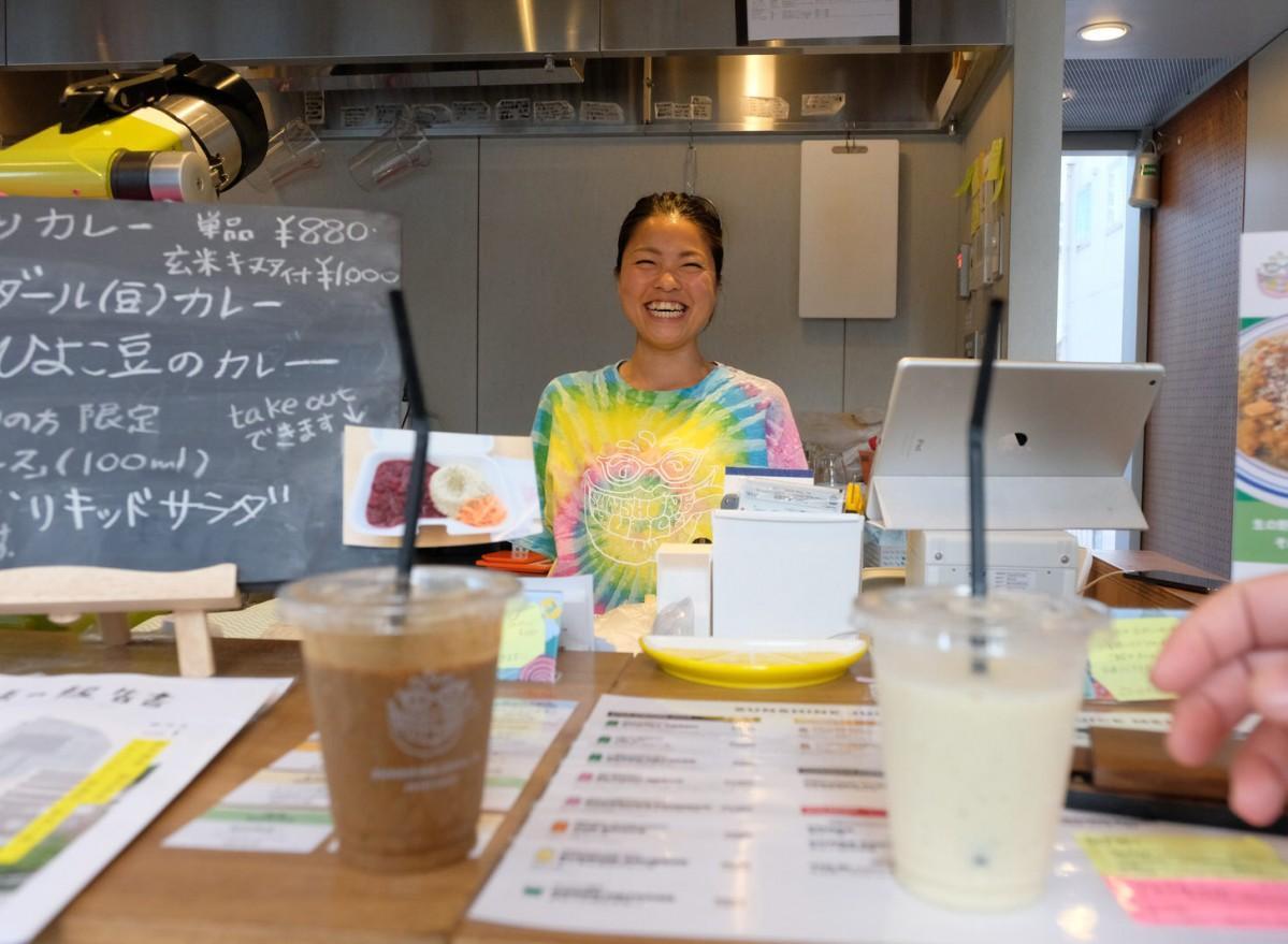 カラフルなロゴが入ったTシャツを着てジュースを提供するスタッフ