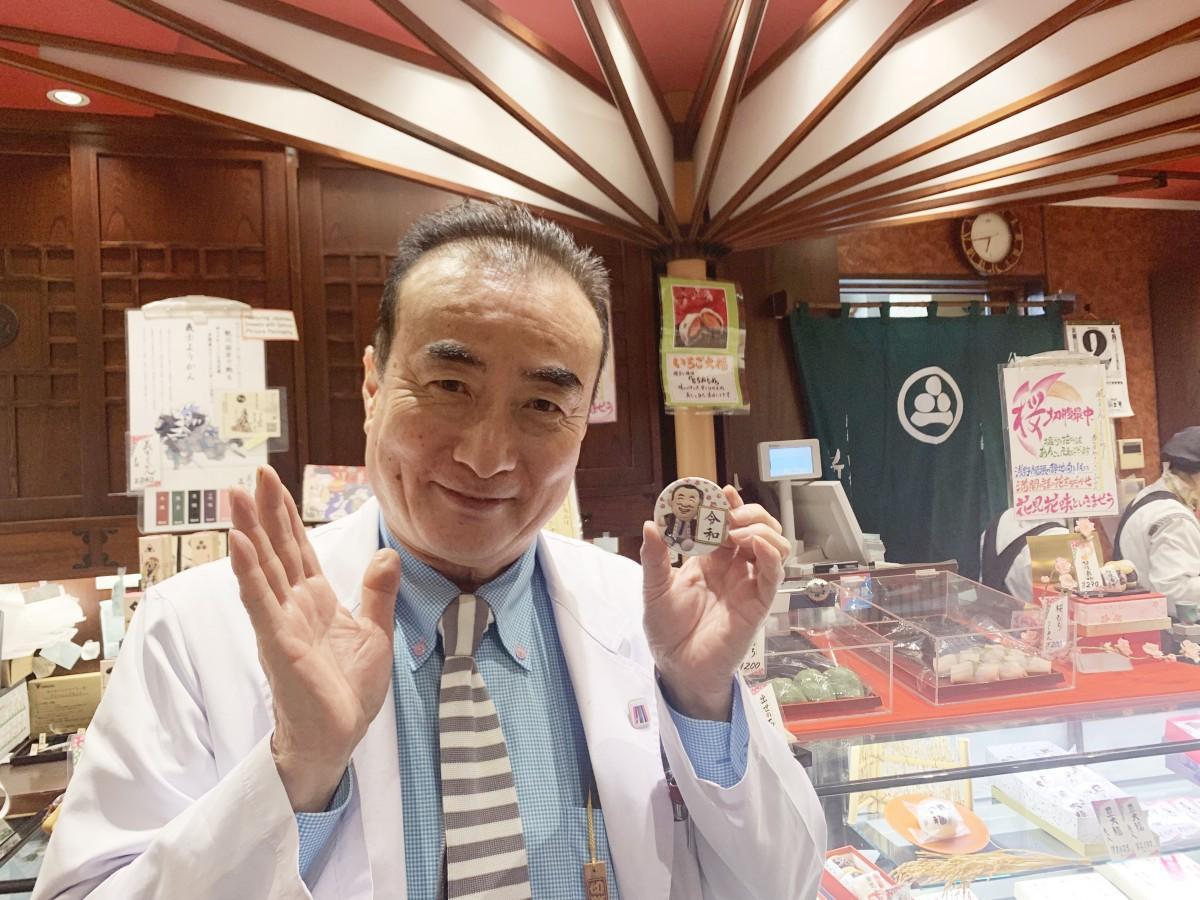 オリジナルマグネットを持つ渡辺仁久社長