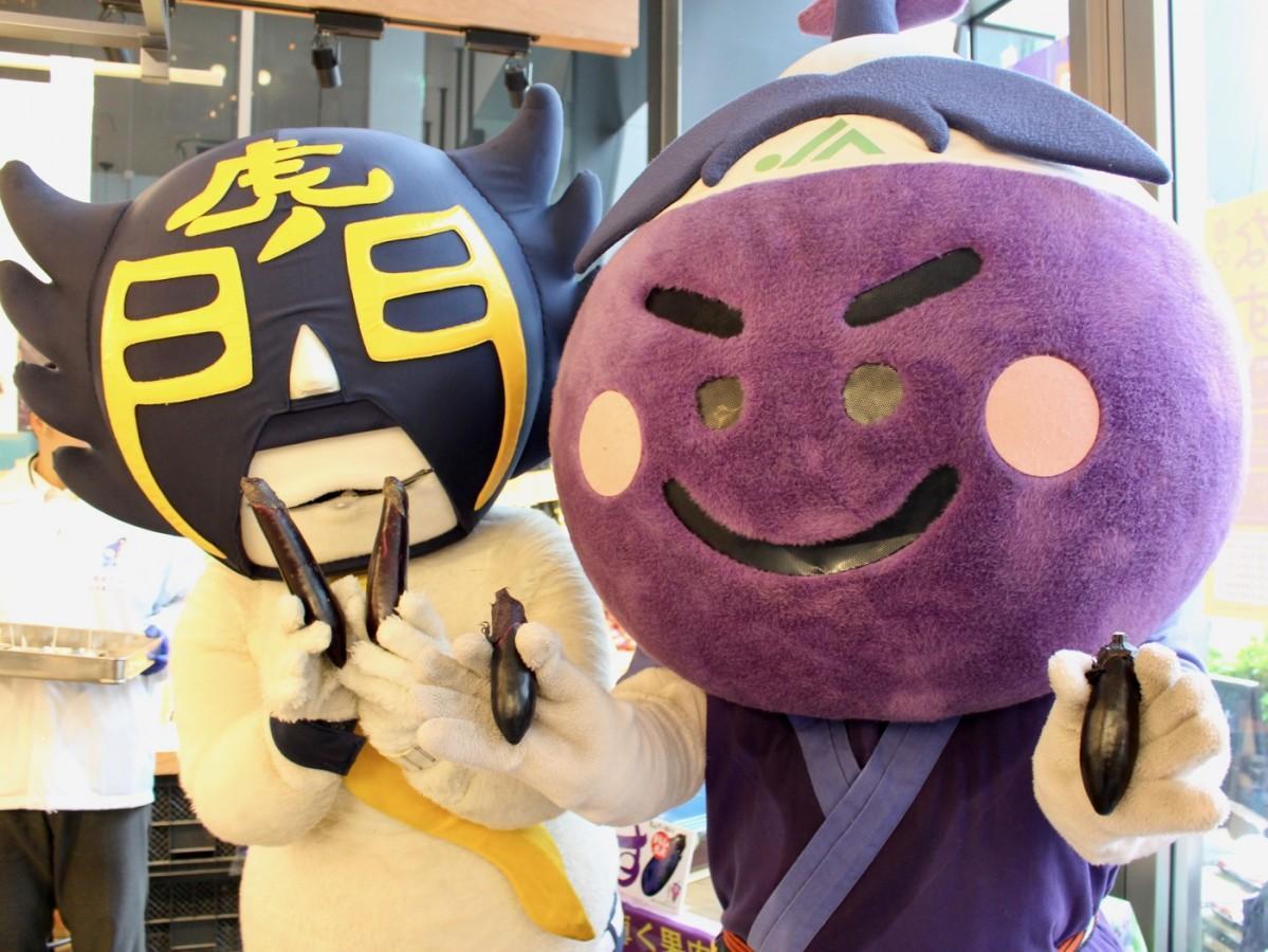 岡山県産千両なすマスコットキャラクターのあっぱれ健紫郎と、地元ご当地キャラのカモ虎課長