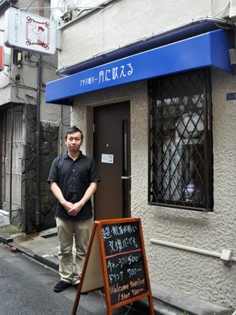 「プチ文壇バー 月に吠える」のマスター、肥沼和之さん。手書き看板には「超・敷居が低い文壇バーです」の文字。