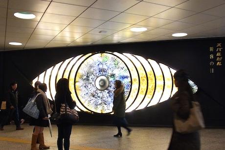 再び明かりがともり回転を始めた「新宿の目」。本来動くということを知らずに驚く通行人の姿も