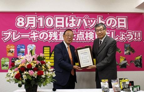 「ブレーキパットの日」を制定した記念日登録証授与式の様子。田村社長(左)と加瀬理事。