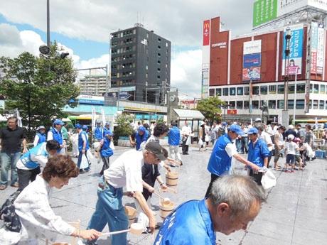 写真は昨年の様子。貸し出されたひしゃくのほか、じょうろやペットボトルを使って打ち水をする参加者も。