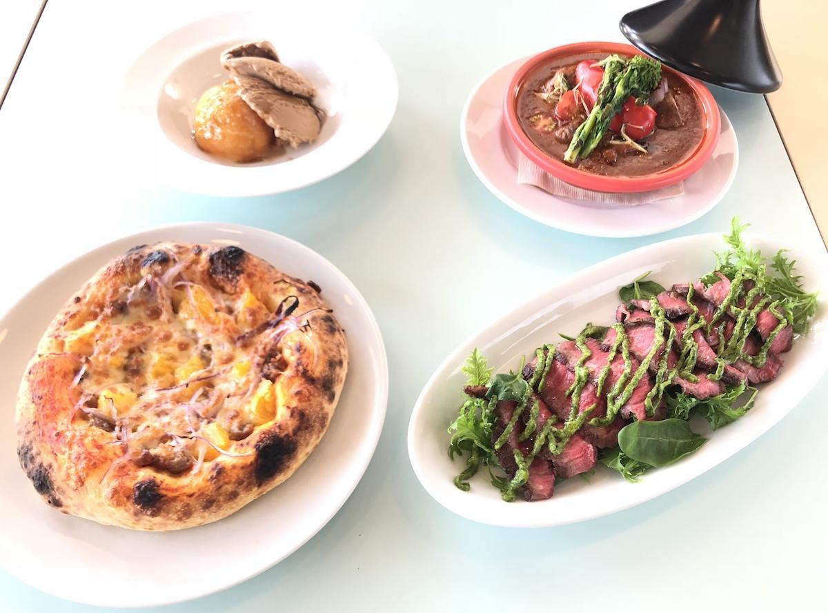 「ベーカリー&レストラン 沢村」が提供する「九州産豚のサルシッチャとデコポンのピザ」、「くまもとあか牛のレッドマサラカレー」など