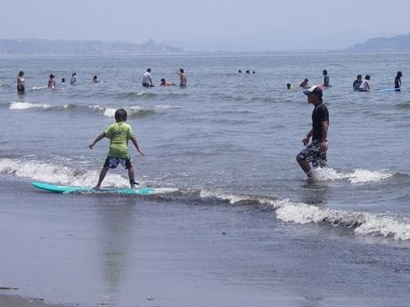 湘南の海でサーフィンを楽しむ親子