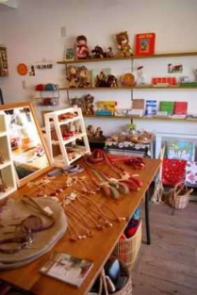 首輪、リード、アクセサリーなどのほか、壁面の棚には絵本の世界から飛び出したようなフェルト人形も