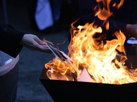 お焚(た)き上げでは住職による読経が響く中、参加者は持参した写真を炉に投じる