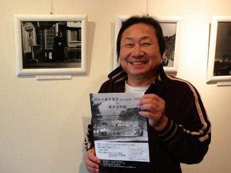 写真展の案内を手にする竹腰さん。自宅でもある酒販店を改装したギャラリーには父・眞一さんの作品も展示されている
