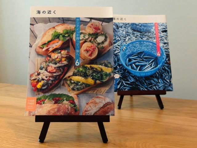 「海の近く」6月号の表紙。鎌倉・大町のベーカリー「mbs46.7」の色鮮やかなサンドイッチが並ぶ。後方は創刊号