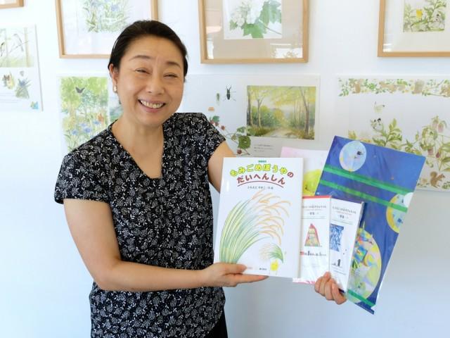 同プロジェクトのきっかけになった絵本作家・ともえだやすこさんの絵本などを手にする西野さん。「病児保育施設の現状を知っていただくきかっけにもなれば」