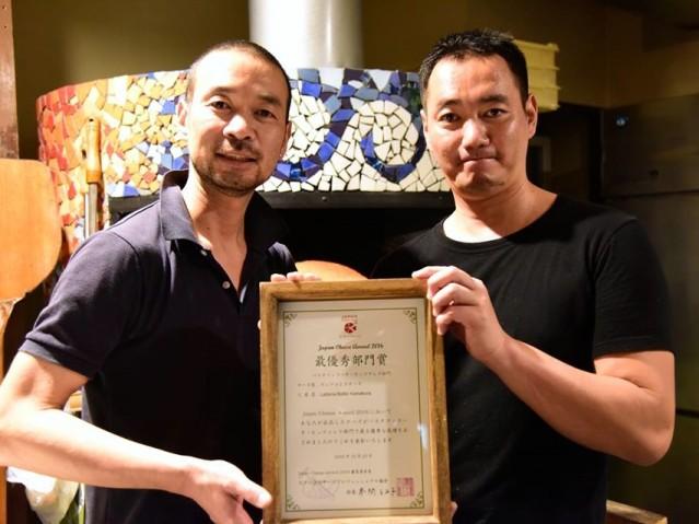 ピザ窯の前でアワードの表彰状を手にするチーズ職人の山崎大志郎さん(右)とピザ職人の兄・山崎健太郎さん(撮影:森川孝郎)