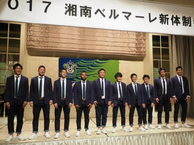 ブルックスブラザーズ製の今シーズンのオフィシャルウエアを着た曺貴裁監督(左から5人目)と新加入の選手たち。「選手を生き生き躍動させる」と同監督