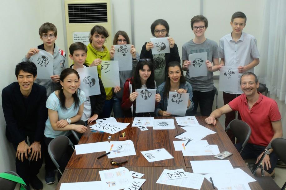 それぞれがレイアウトして筆で塗った印鑑デザインの用紙を手にする中高生たち。前列左端がかまくらはんこの月野さん、隣が加藤先生