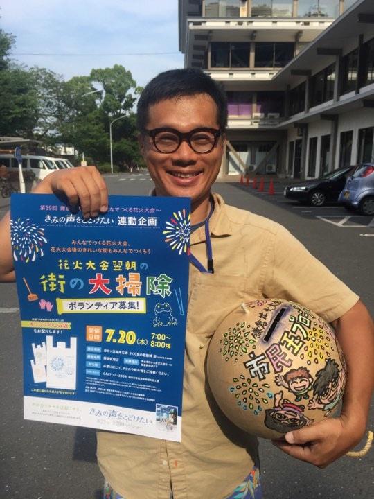イベントのポスターと花火大会の募金箱「市民玉」を手にする林さん。「花火はキレイ。翌朝、街もキレイ」が合言葉