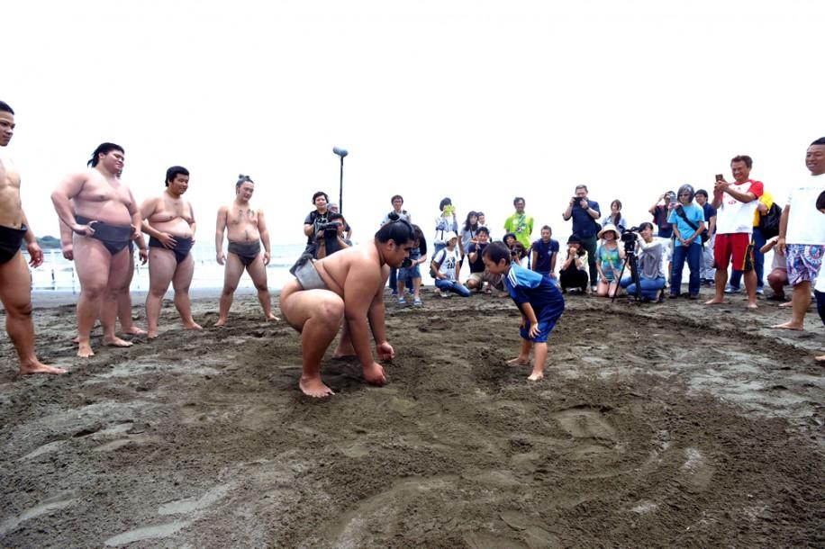 ビーチクリーン後に全員で作った砂浜の土俵で力士と子どもが対戦