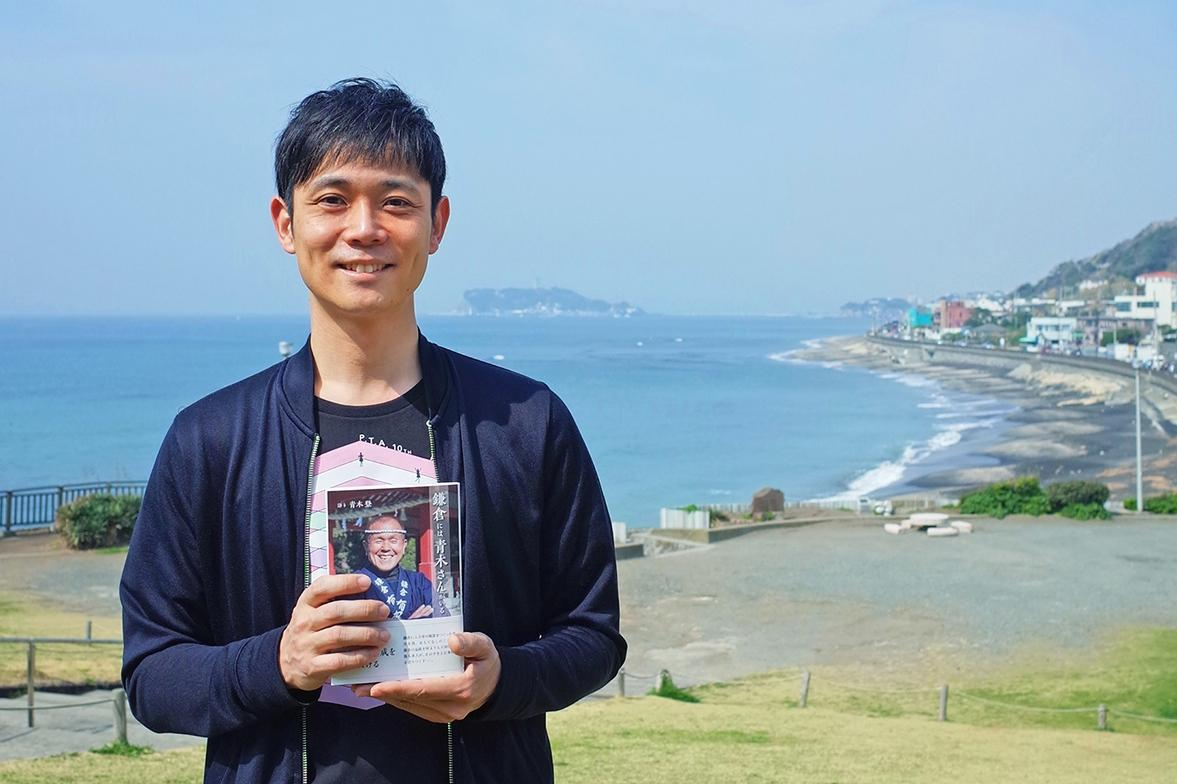「青木さんの35周年と35歳の自分との縁も感じる」と本書を手にする古谷さん。「物としての本が大好き。ぜひ注文、購入は書店を通して」と呼び掛ける