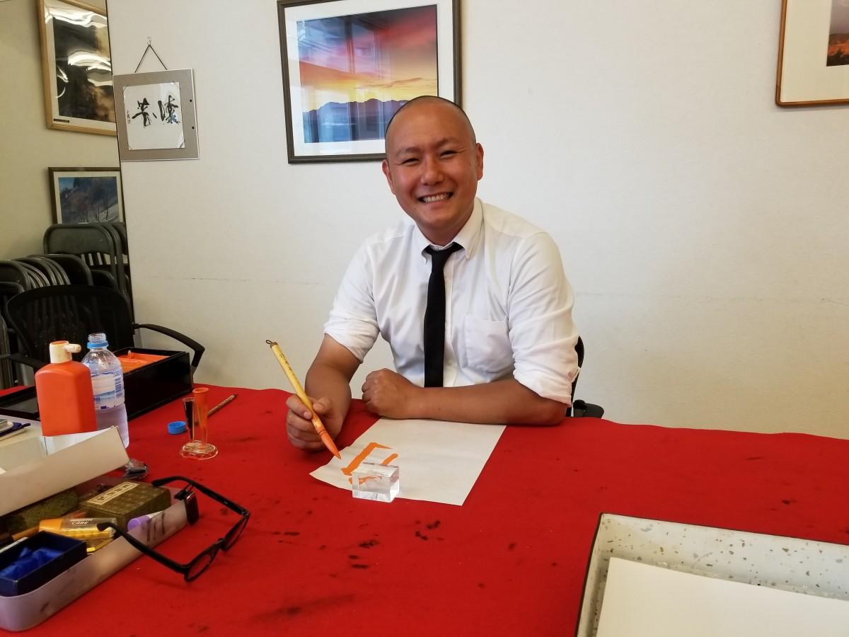 笑顔で筆を持つ中島白隆(はくりゅう)さん